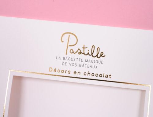 Pochette pour décors en chocolats – Dorure à chaud or brillant logo, cadre – découpe à la forme – Olin 400gr/m2 Blanc Naturel